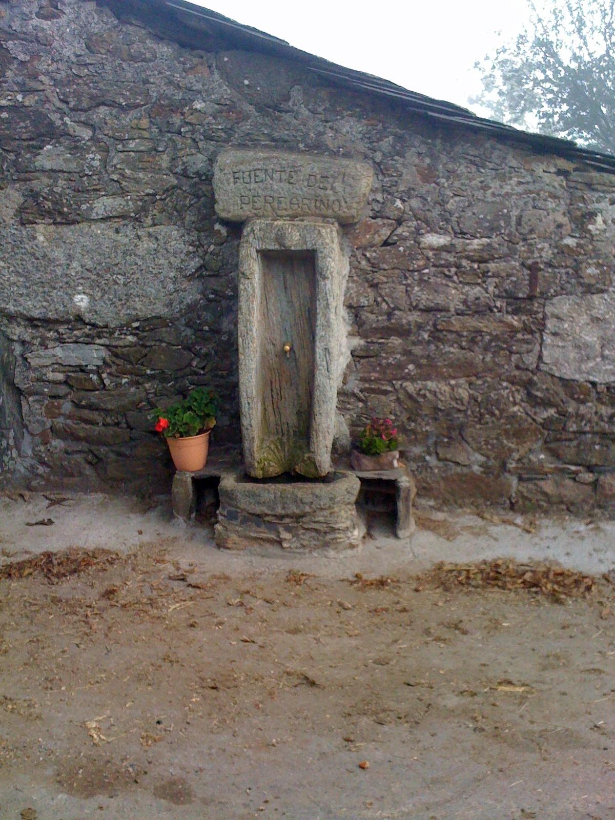 ein schön gestalteter Pilgerbrunnen am Weg